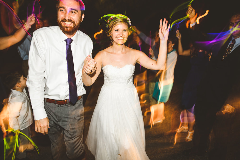 037 - bride and groom exit the wedding with neon glow sticks.jpg
