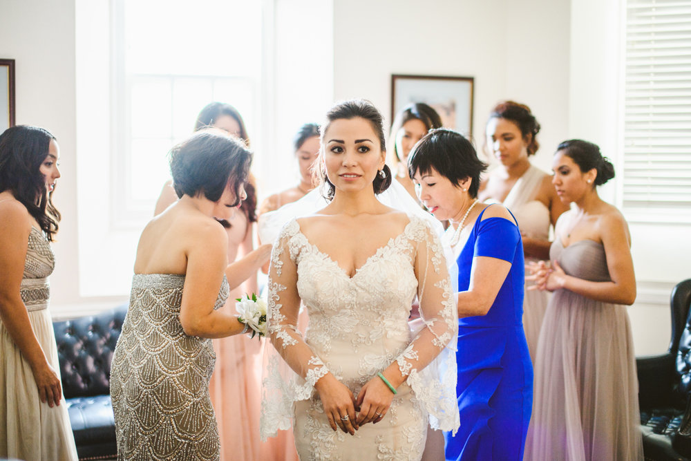 001 bridesmaids and mother of bride helping bride into dress.jpg