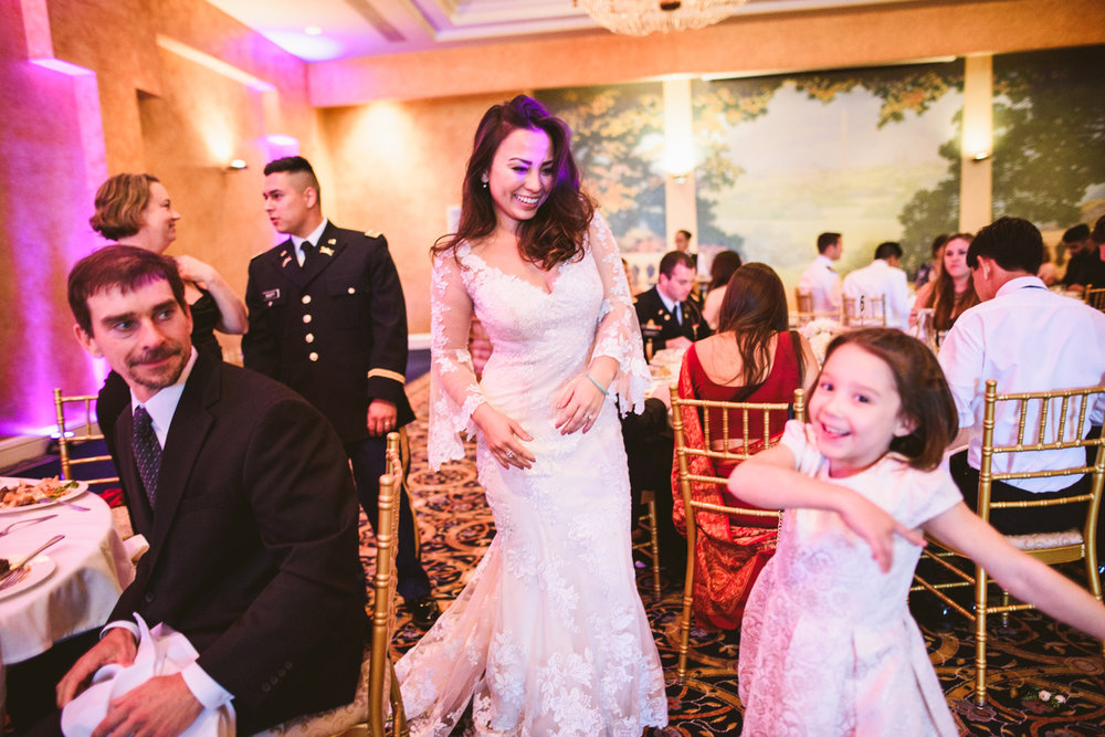 017 bride laughs at kid at wedding reception at fort myer.jpg