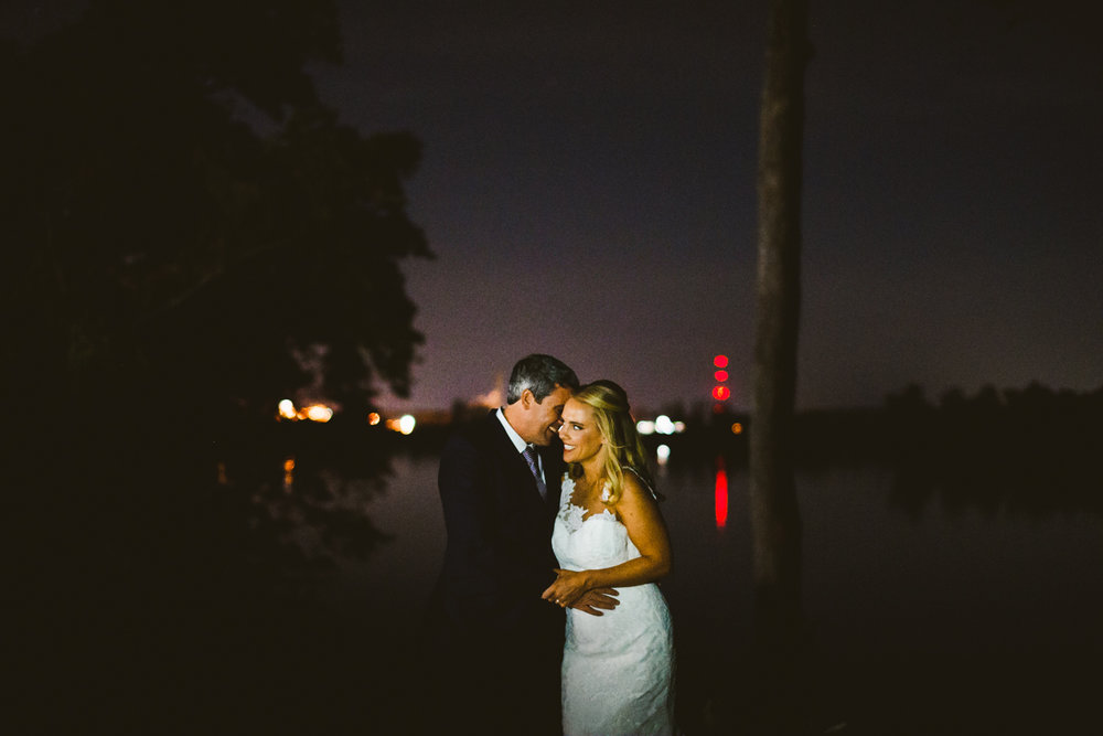 018 - night portrait of the bride and groom smiling next to the james river.jpg