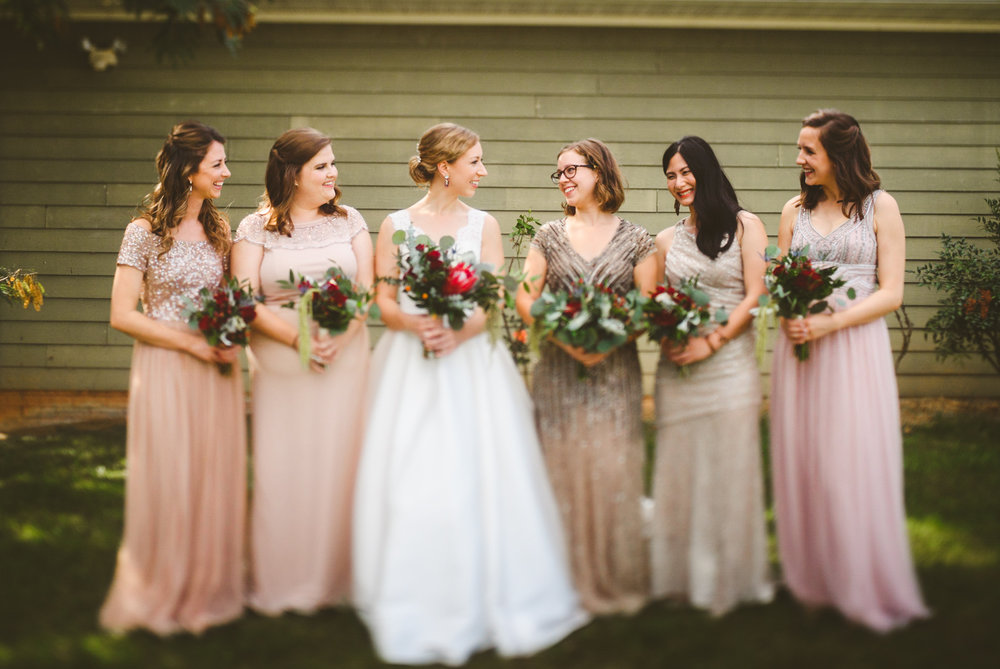 004 - bride and bridesmaids looking at each other and laughing as they carry their bouquets.jpg