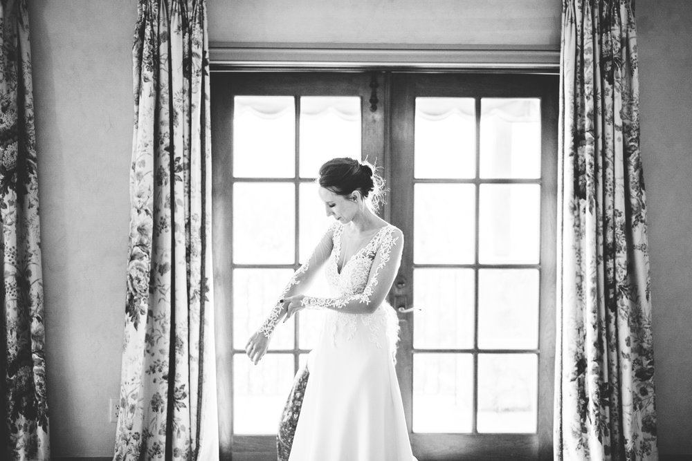 013 - black and white of bride adjusting her wedding dress.jpg