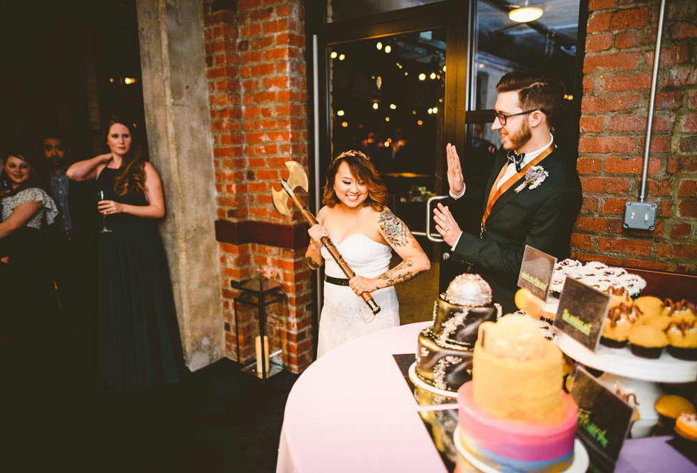 036 - bride prepares to cut the cake with a giant wedding axe.jpg