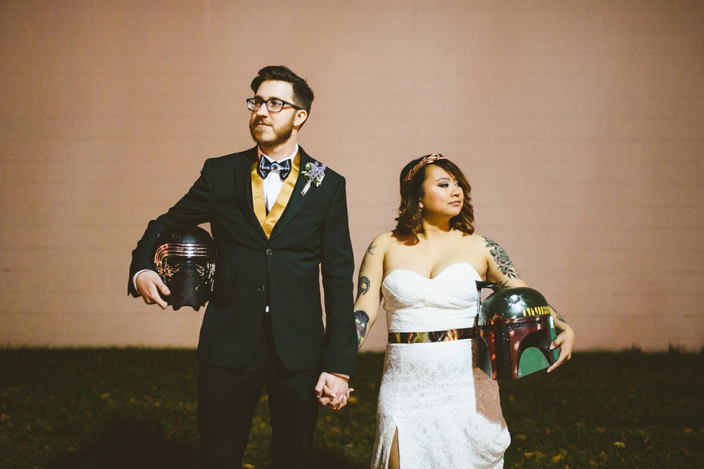 042 - bride and groom pose with kylo ren and boba fett helmets during night portraits in richmond virginia star wars wedding.jpg