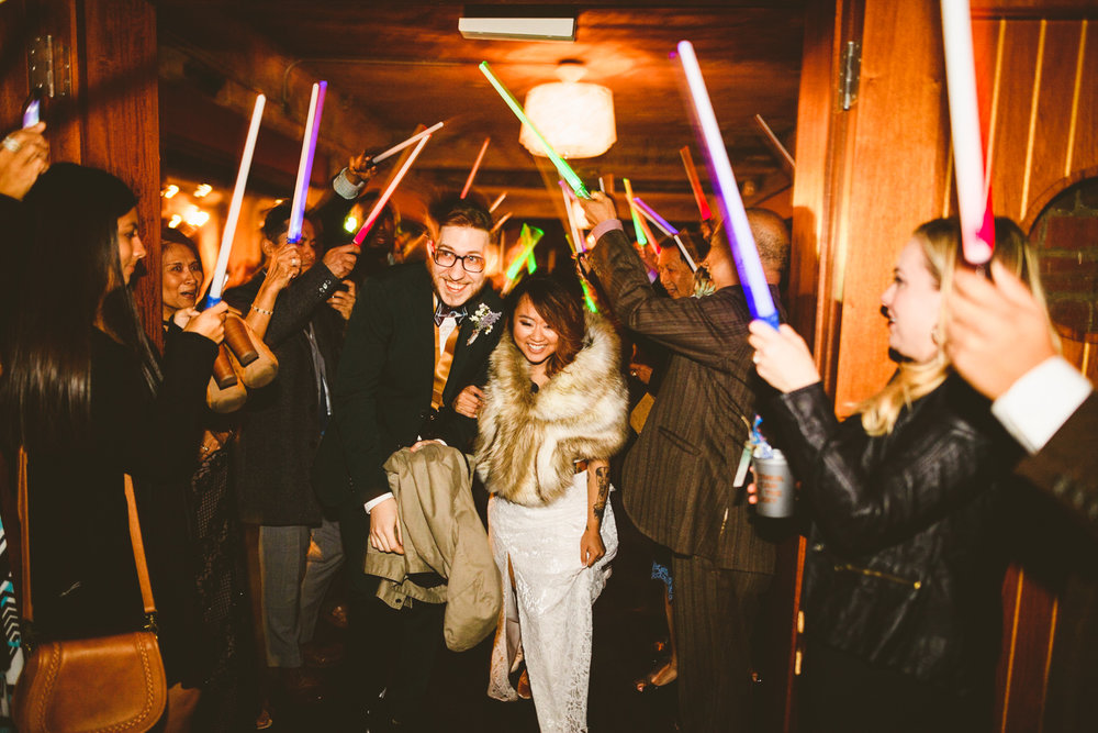 046 - bride and groom exit their wedding with lightsabers.jpg