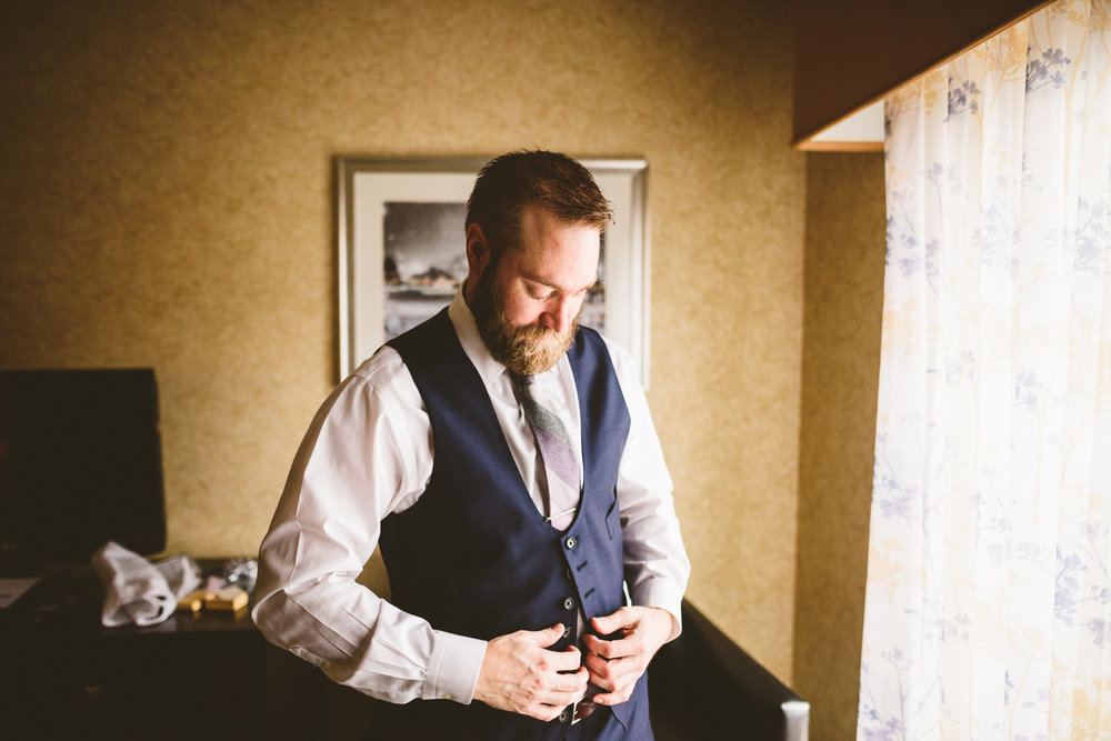 011 - groom puts on vest.jpg