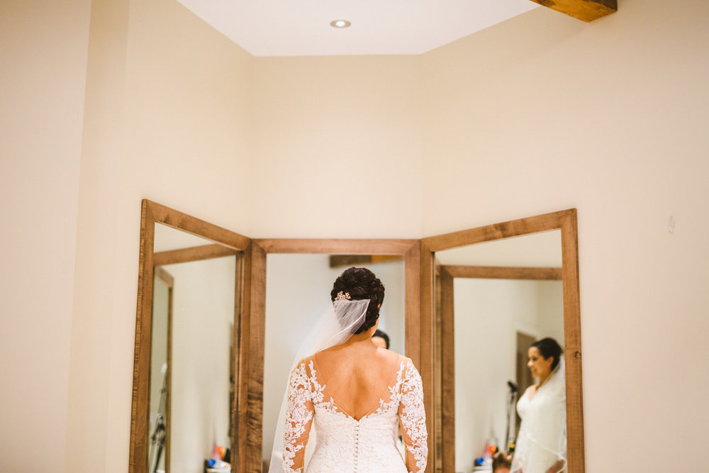 016 - the back of the bride's dress as she looks in a big mirror.jpg