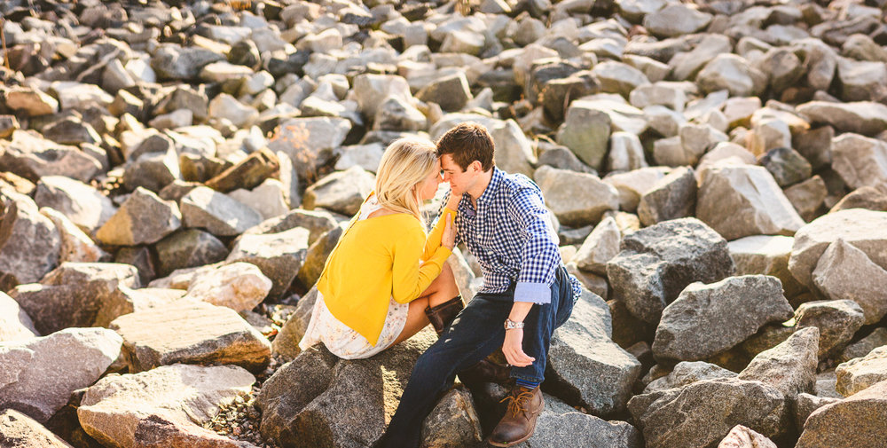 005 - engagement session couple sits down on rocks and looks into each others eyes.jpg