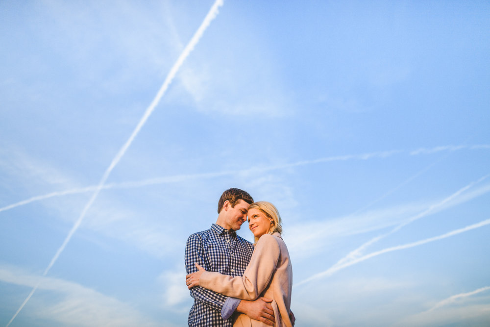 013 - couple looks out against blue sky with jet trails behind them.jpg