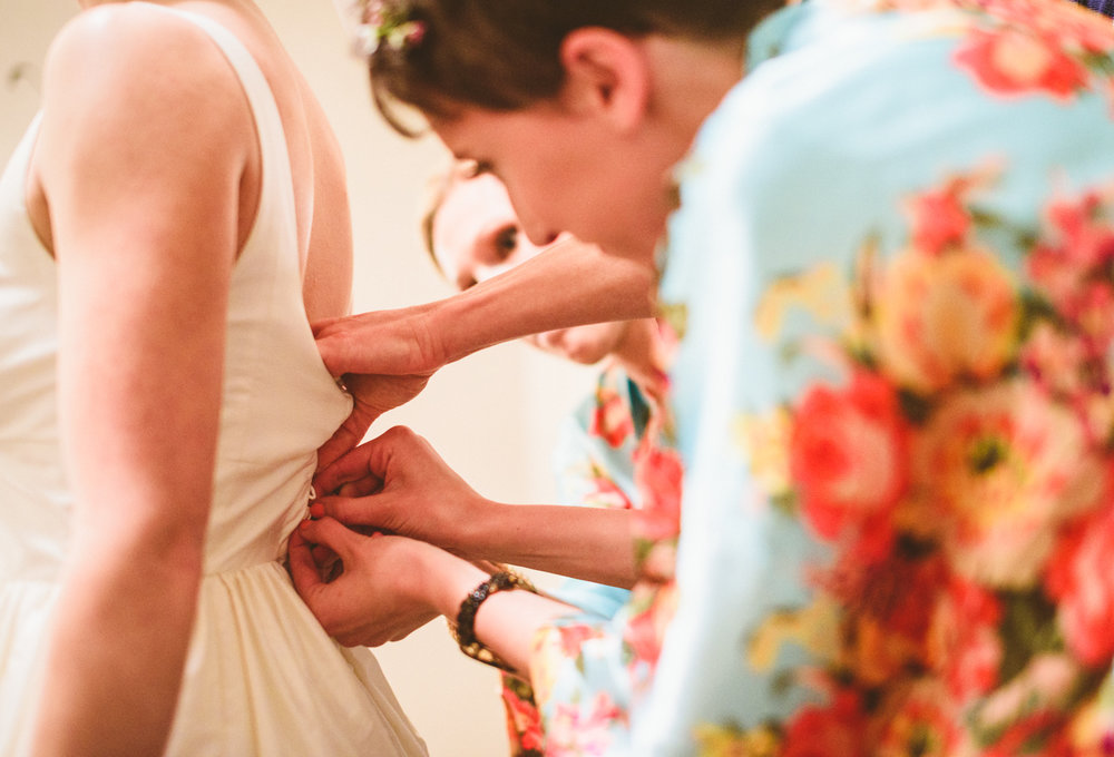 003 - bridesmaids hands as they help her button up bride's wedding dress.jpg