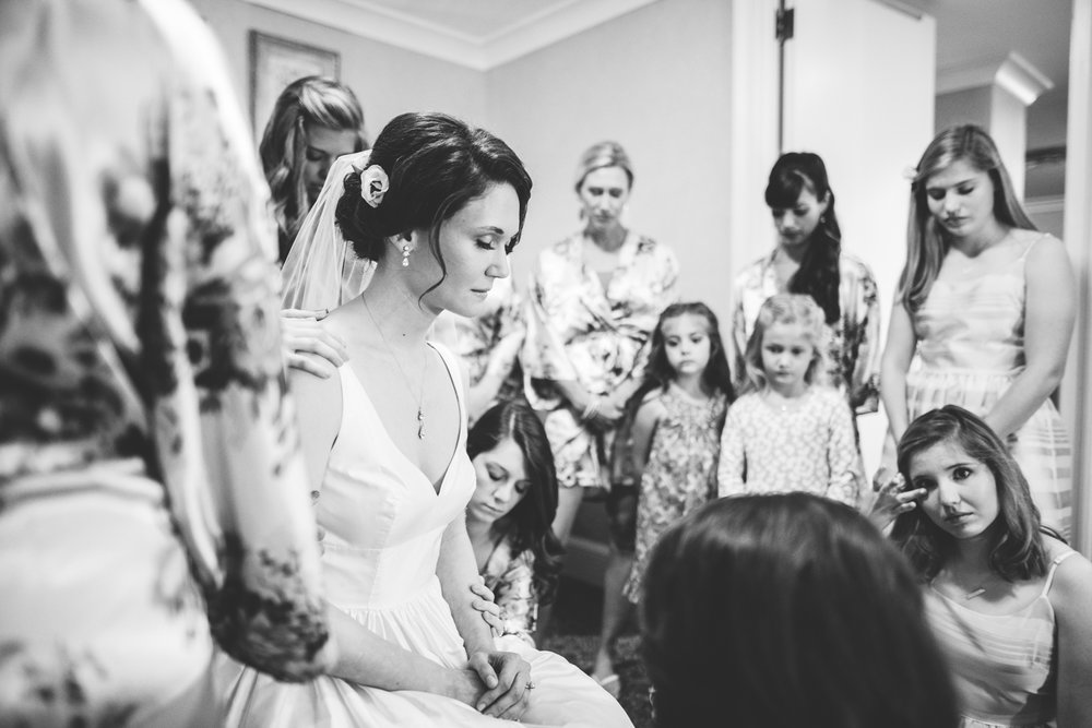 005 - bride being prayed for right before her wedding as her bridesmaids lay hands on her.jpg