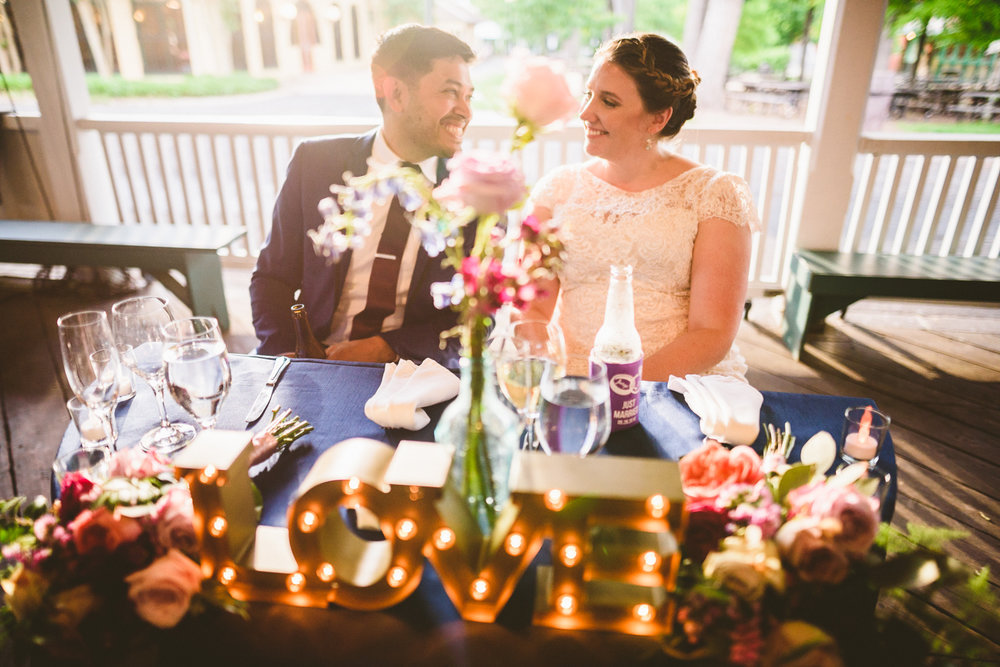 015 - bride and groom laugh with each other at the sweetheart table with Love sign in front of them.jpg