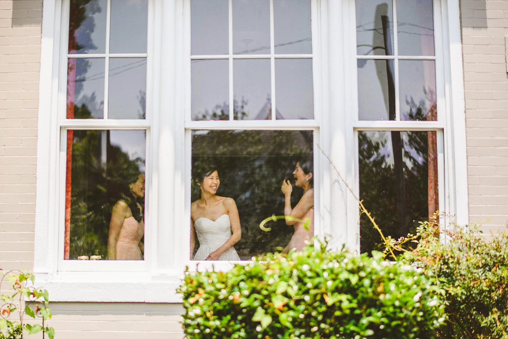 007 - bride laughing with her bridesmaids through a window.jpg