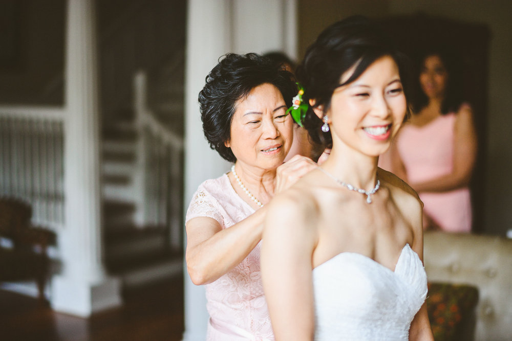 009 - mother of the bride putting a necklace on the bride's neck.jpg