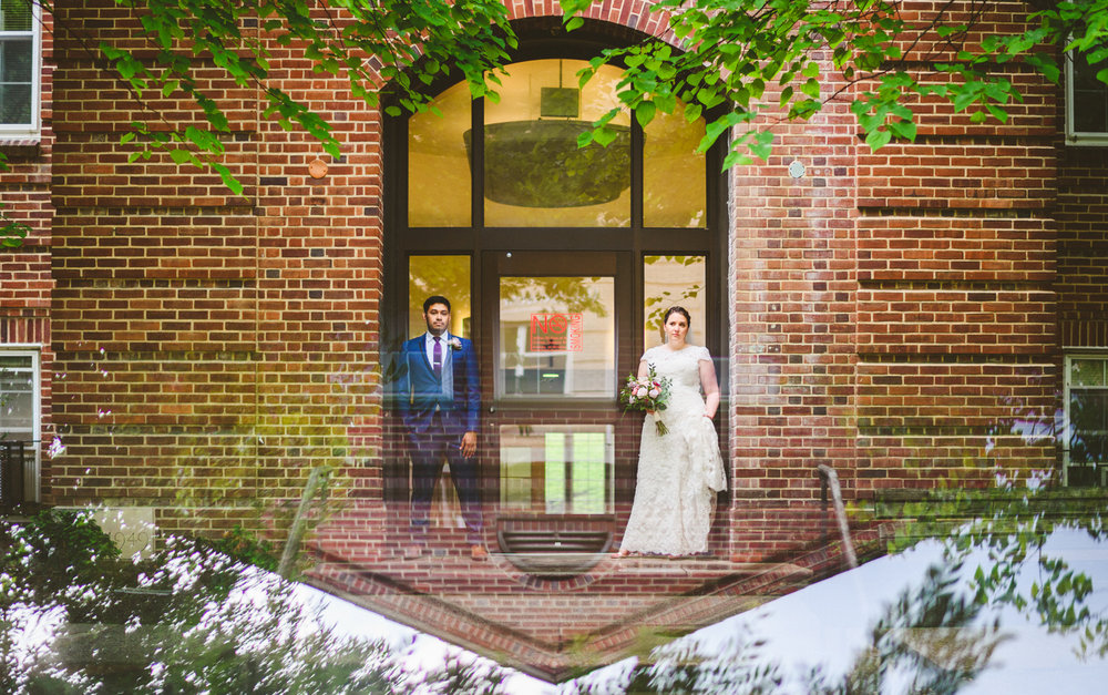 039 - reflection of bride and groom next to brick building.jpg
