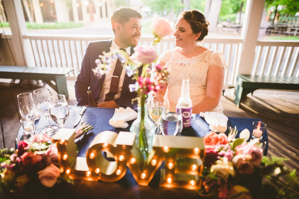 041 - bride and groom laughing at sweetheart table.jpg