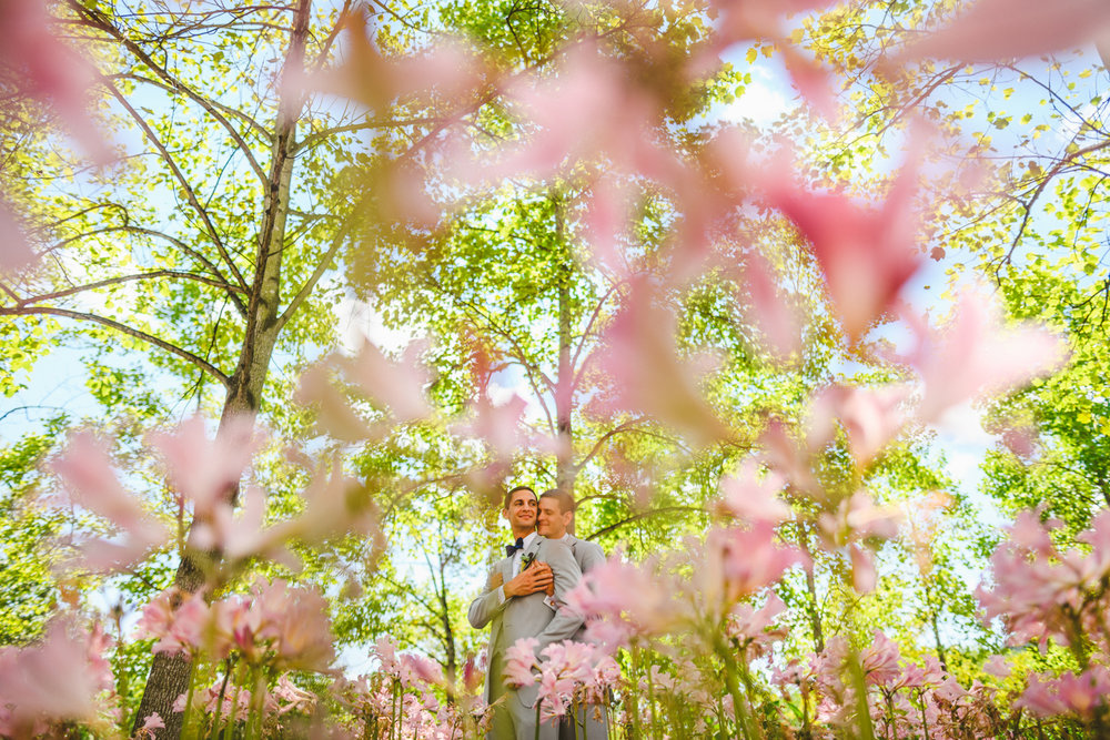 069 - couple in front of pink flowers gay wedding maryland.jpg