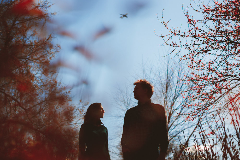 008 - silhouette of engaged couple with plane flying in the background.jpg