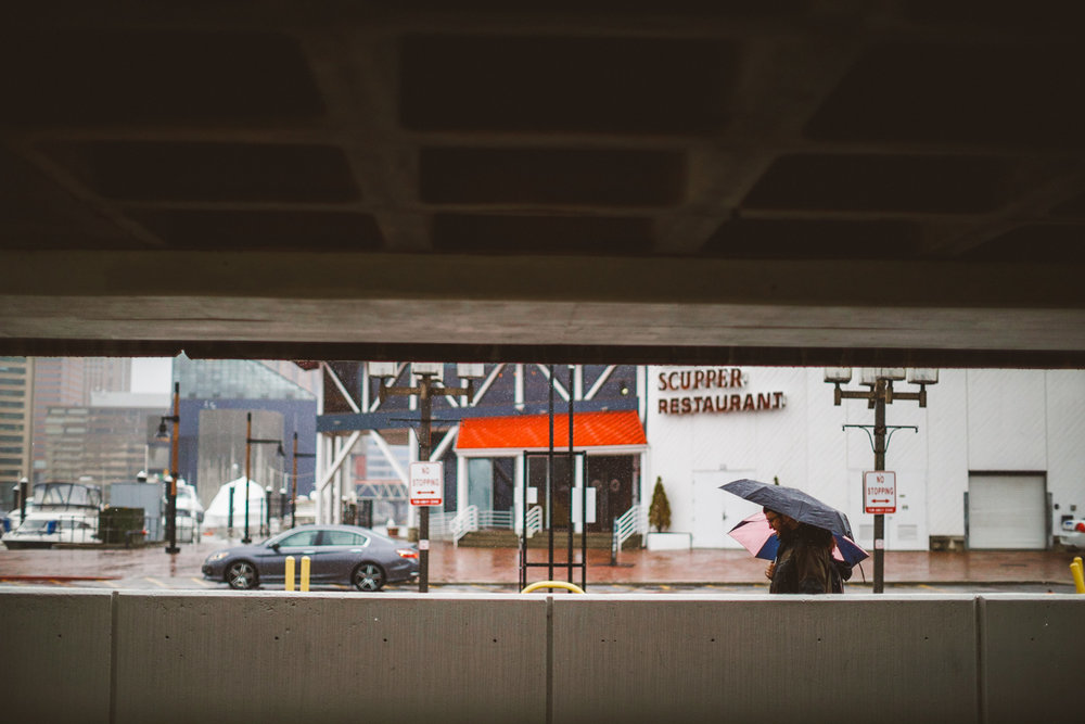 007 - couple walking together with umbrellas baltimore rusty scupper.jpg