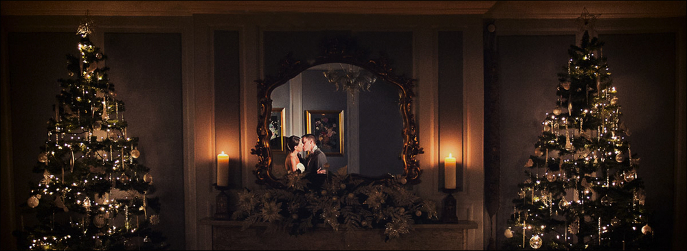 Christmas wedding photograph made panoramic of the couple kissing in a mirror