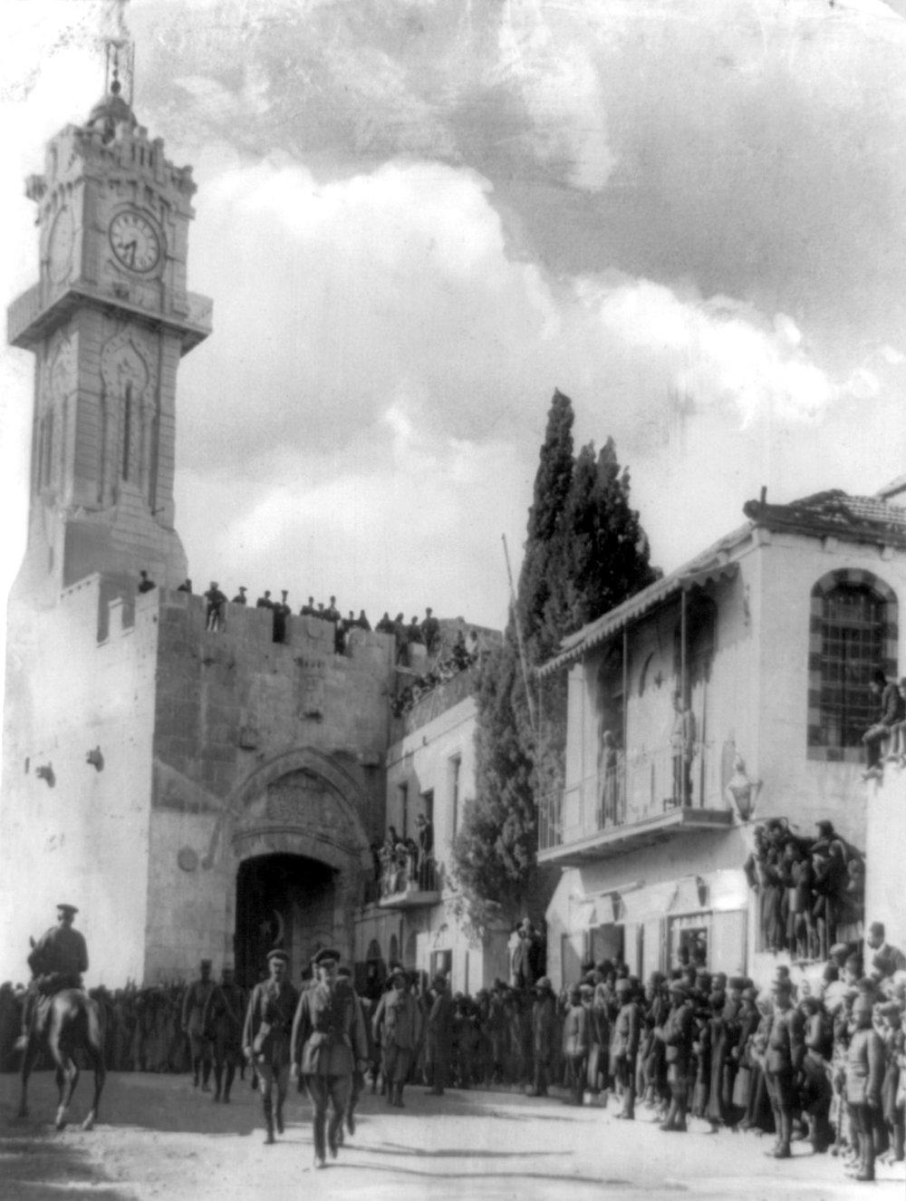 General Edmund Allenby spaserer inn Jaffa-porten 11. desember 1917. Klokketårnet i bakgrunnen er no borte.