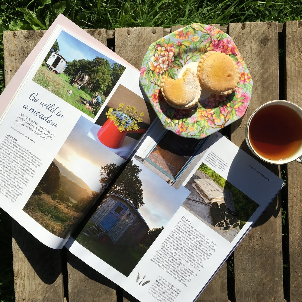magazine on table with cake, tea and sunshine
