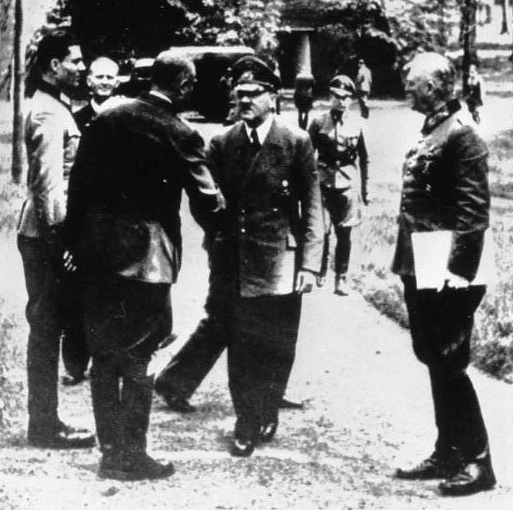 Claus is on the left, standing at attention in front of Hitler.