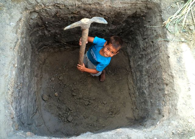 A young member of the El Pilon community helping to construct a pit toilet