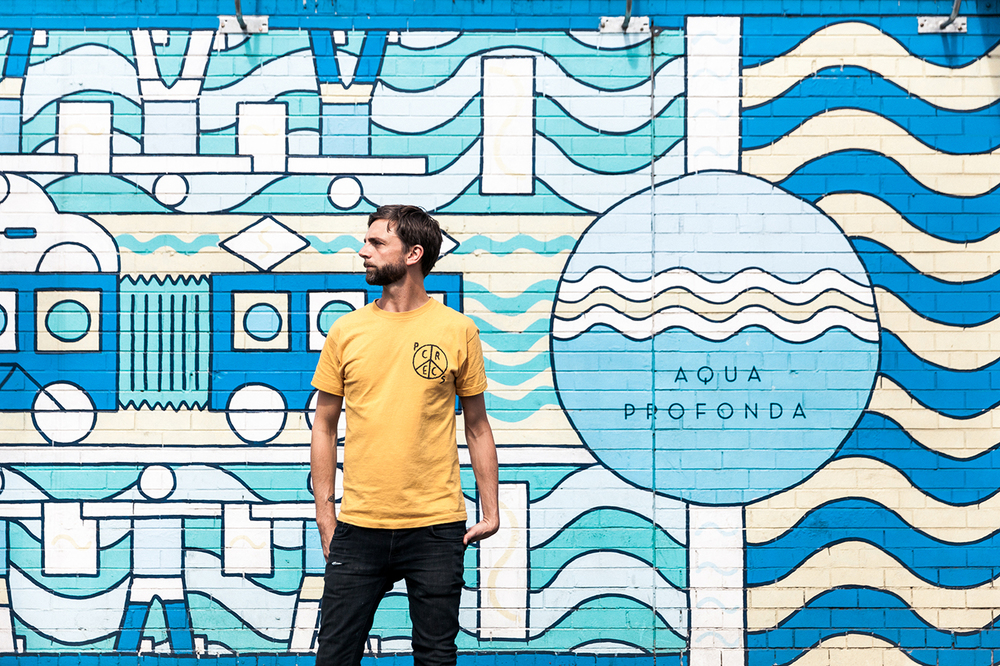 Stephen Baker stands in front of Aqua Profonda Mural
