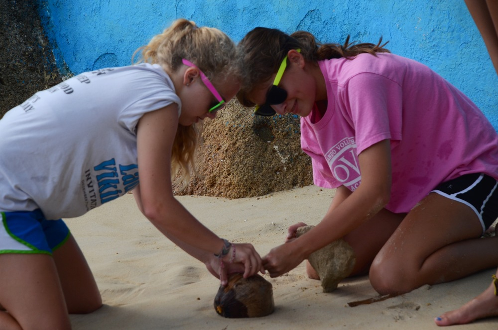 Anna Grace and Aurey trying to break open a cocnut.