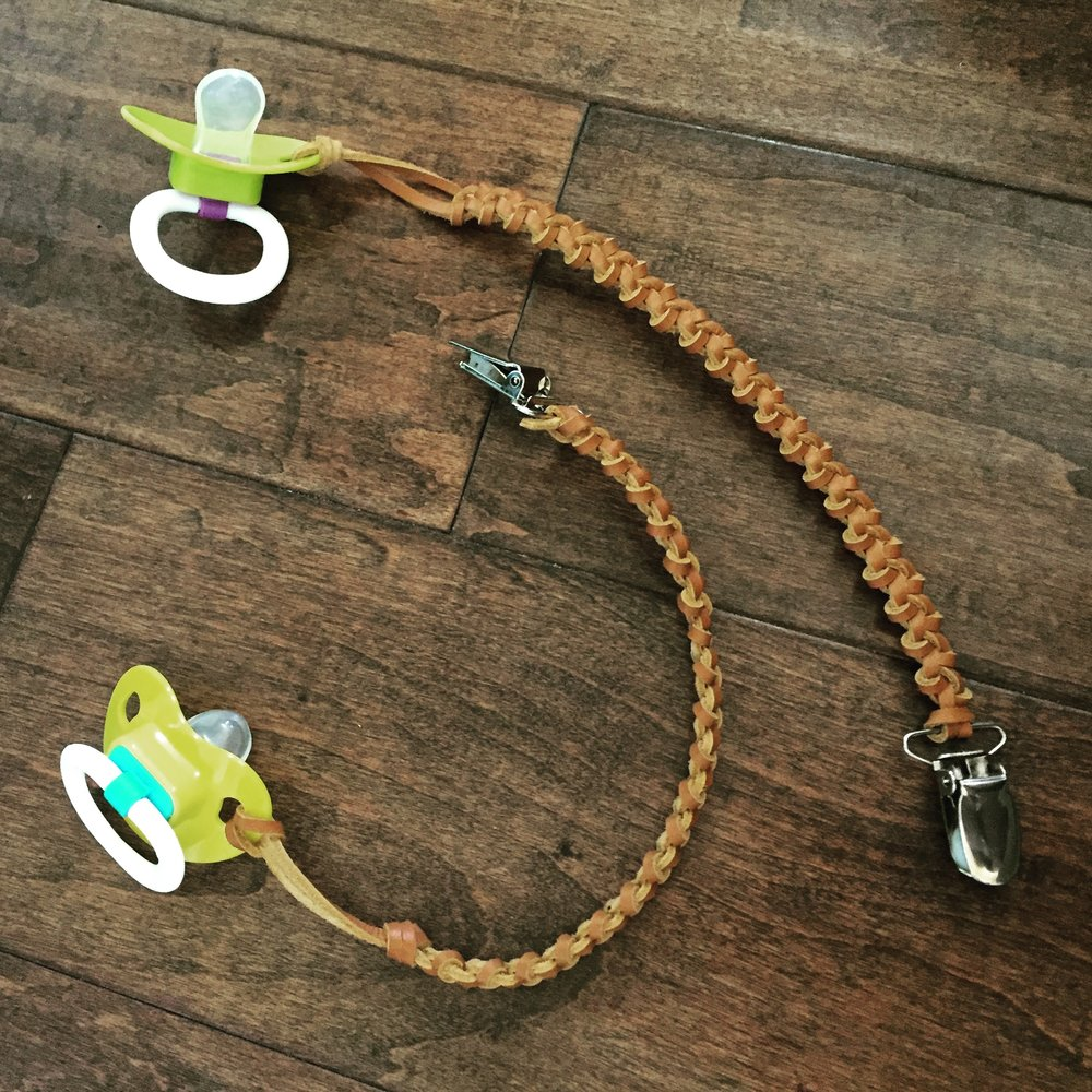 FOR SALE - Pacifier Lanyards (above) Braided Leather Lace with Brass colored Clip (silver is shown). Pacifier(s) not included! Choose the color: Light Brown (shown), Dark Brown, or Black. One for $7 or Two for $12.  Want more, email me for a quote. ($7 shipping within the US & sales tax applies to UT residence) Email me at:  CircleM@outlook.com