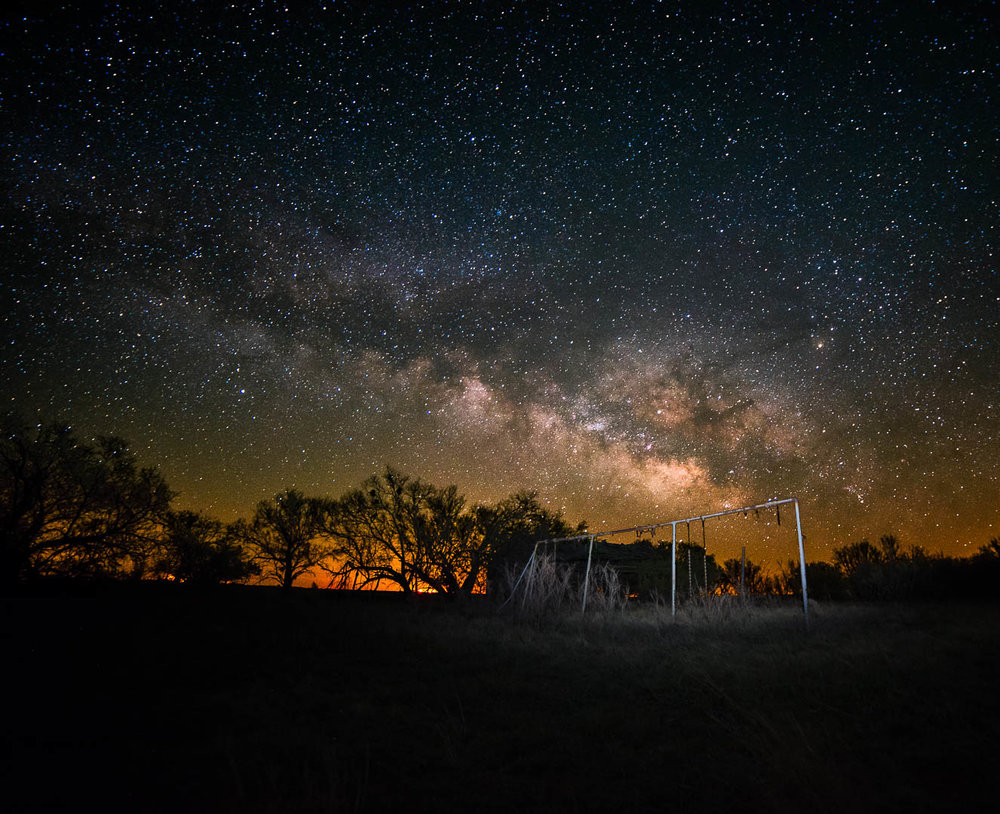 The Milky Way rises over an old swing set and an out building of an abandoned school, and the lights of the windmills an Seymour TX in March 2017.  2 frames ikon D750 Rokinion 14mm 3200 ISO f2.8 25 seconds