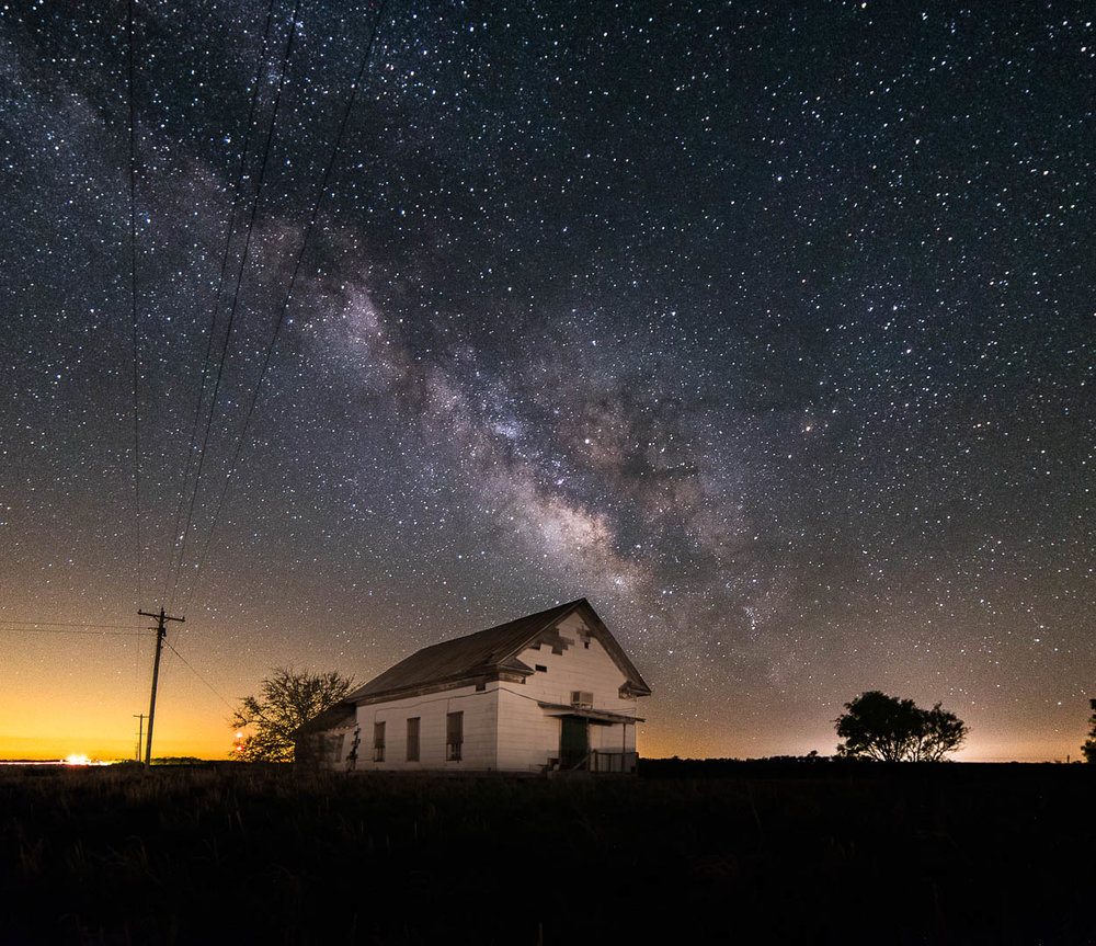 The Milky Way rises over an old church lit by passing vehicles between Olney and Loving TX in March, 2017.  2 frames Nikon D750 Rokinon 14mm 3200 ISO f2.8 15 seconds