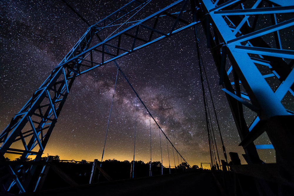 Milky Way over the Regency Suspension Bridge near Mullin Texas in the early morning of 04/27/2017  1 frame Nikon D750 Rokinon 14mm 3200 ISO F2.8 20 seconds  Foreground lit from 100' away with an LED flashlight reflected off the bridge's cable anchor block.