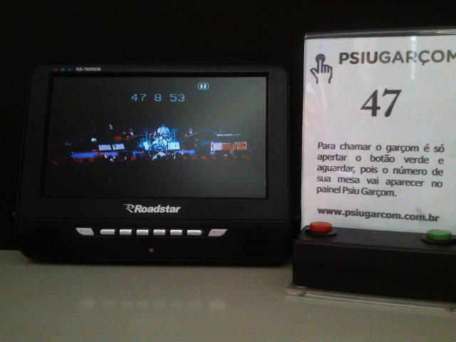 As senhas dos chamados dos clientes aparecem na parte superior da tela, sem interferir na visualização das imagens exibidas pela TV (Foto: Divulgação)