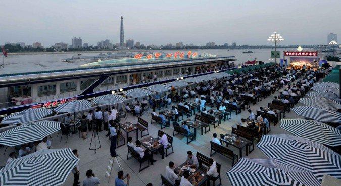 Festival é realizado ao lado de um restaurante flutuante iluminado, nas margens do Rio Taedong (Foto: Reprodução)