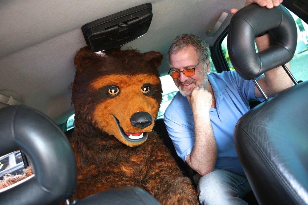 """Carneiro """"convidou"""" o Urso, personagem fictício e mascote da cervejaria, para embarcar ao lado dele no primeiro Uber que circulou pela cidade paulista (Foto: Divulgação)"""