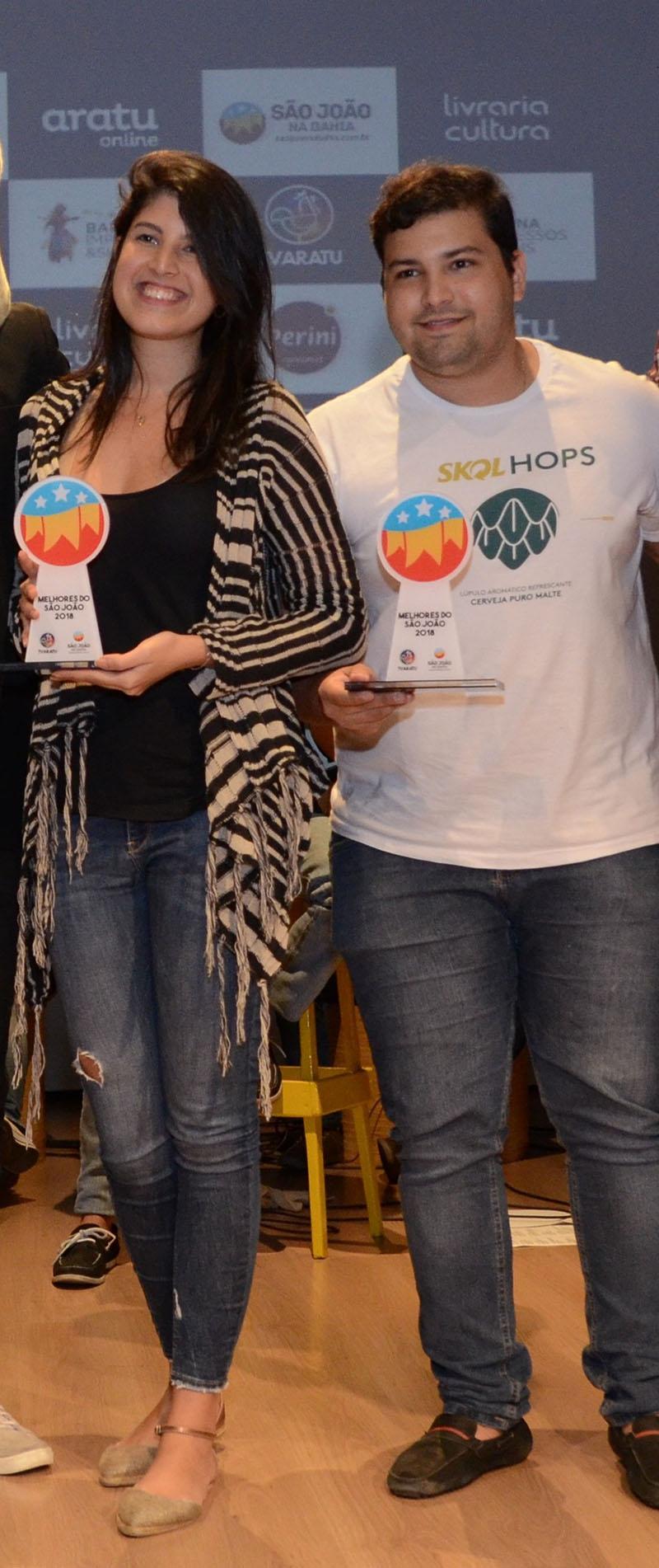 Maria Eduarda Barreto, gerente regional de marketing da Ambev, e Aécio Lacerda, assistente de trade marketing, exibem os troféus (Foto: São João na Bahia/Divulgação)