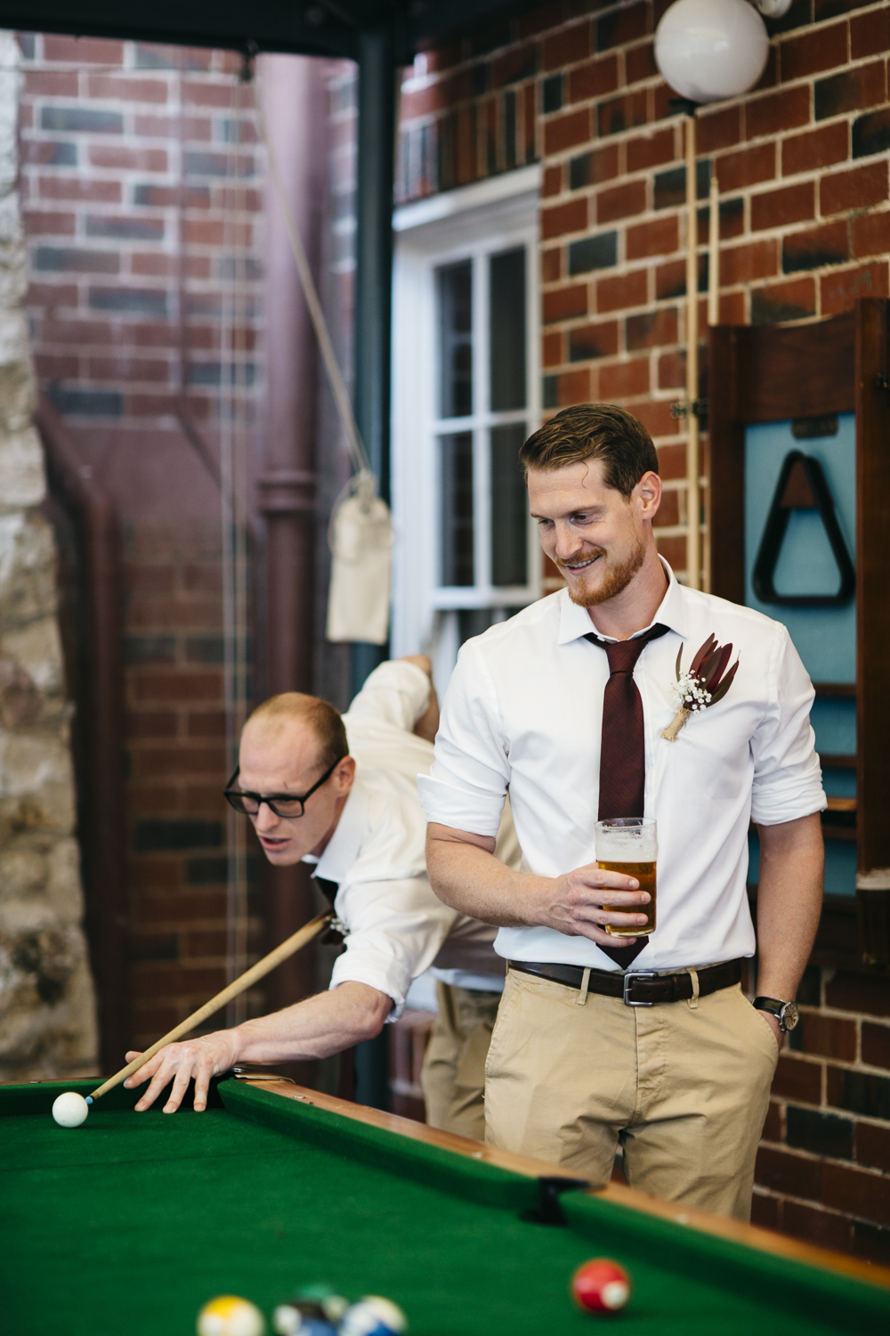 Groom plays pool at Caves House Yallingup
