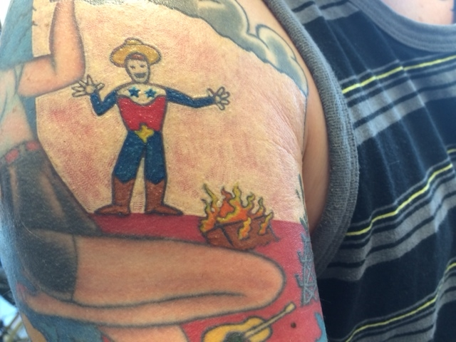 A customer's Texas-themed tattoo. Yup, that's Waco on fire.