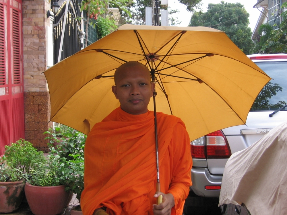 1207-phnom penh monk with umbrella calling for food offerings (1024x768).jpg