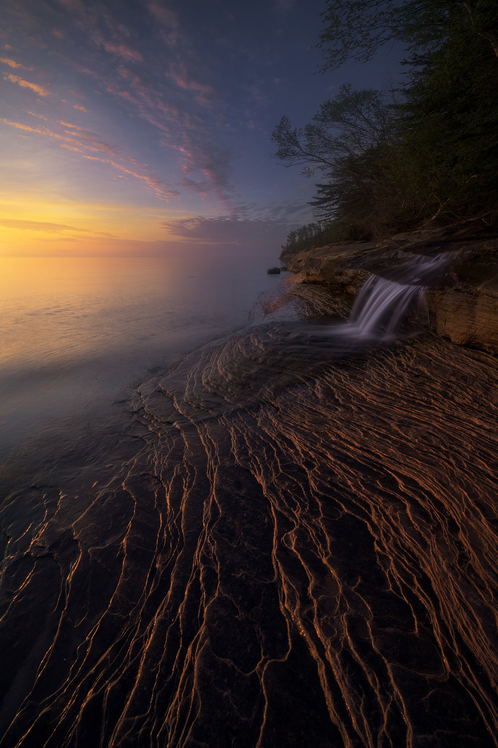 """Northern Reach""    Waterfall on the shores of Lake Superior. Irix 11mm at f/16, 1 second. In this case 11mm was really helpful, as the clouds were arcing high overhead, and the prominent foreground ridges lended themselves well to the wide view, adding lots of depth to the scene. I was probably less than 10 feet from the waterfall!"