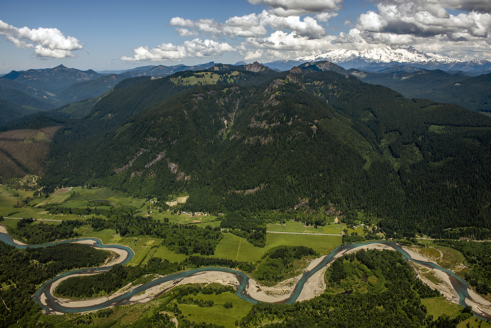 In this aerial photo taken on Thursday, May 28, 2015, Mount Rainier looms to the north as the Cowlitz River winds its way through Randle, Wash. and the Cowlitz River Valley.