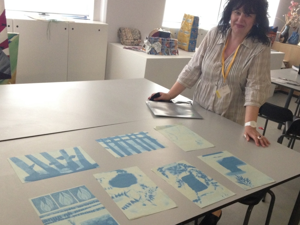 Top row: Students' experiments in cyanotype photograms exposing in the natural light of the classroom. Bottom: Guest artist, and vintage photograph expert, Laura Hickman checking exposure levels.