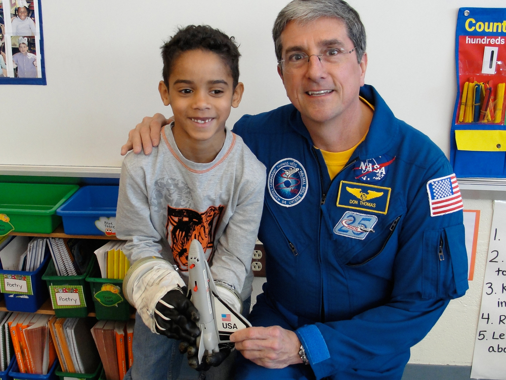 Trying on an actual space glove in the classroom.