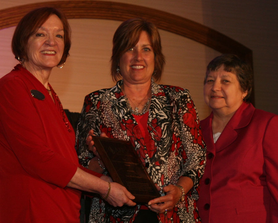 AAFCS 2013-14 President Peggy Wild, CFCS, (far left) and AAFCS Treasurer Sister Victoria Marie Gribschaw, S.C., CFCS, present Michele Cuppy (middle), president/CFO and  co-founder of Sew Much Comfort, with the AAFCS 21st Century Community Champion Award during the AAFCS 105th Annual Conference in St. Louis, Mo.