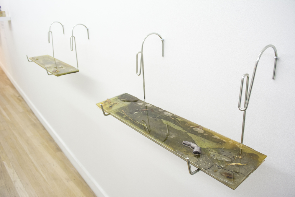 "Mia Goyette  (LEFT)  Windowbox (Complaints) , 2014   Pigmented polyester resin, concrete, cigarettes, necklace, dead leaves, various refuse, steel brackets, 22.5"" x 10.5"" x 10.5""      (RIGHT)  Windowbox (Daily Pain) , 2014   Pigmented polyester resin, concrete, life-cast plaster, dead leaves, various refuse, steel brackets, 22.5"" x 10.5"" x 10.5"""