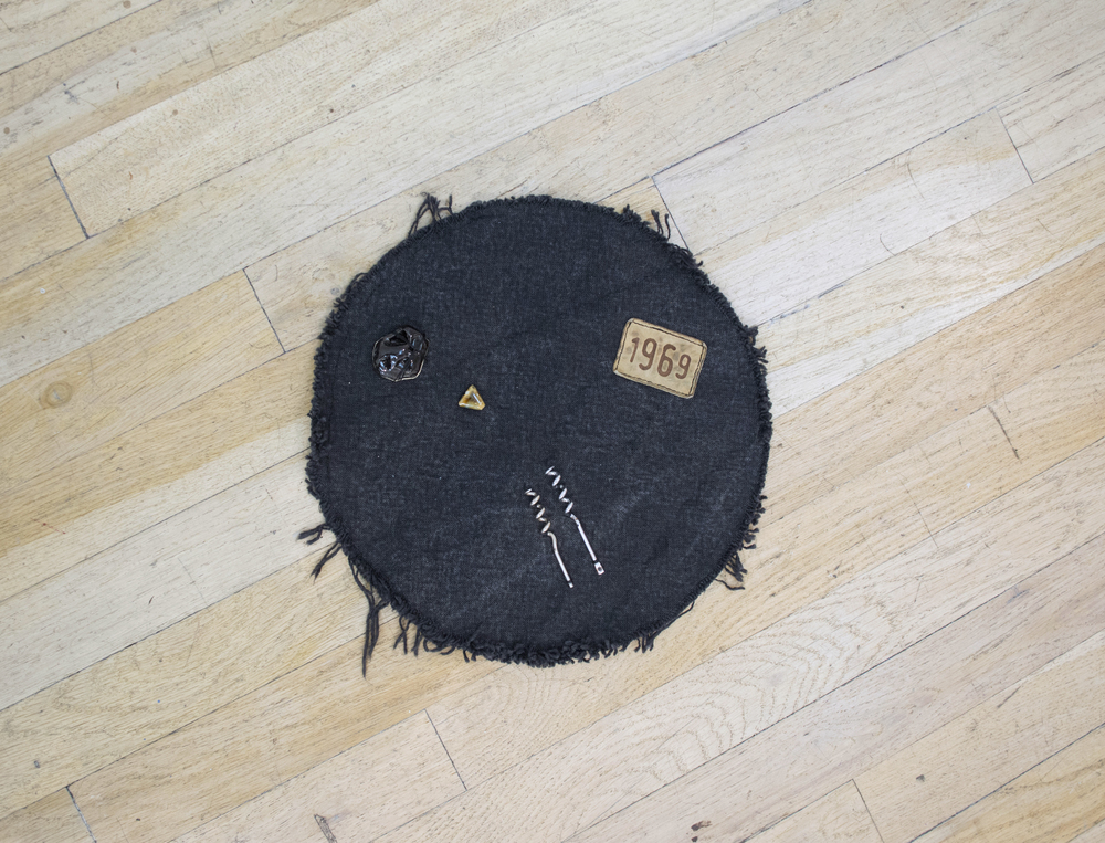"Catherine Czacki   Post radical , 2016  Denim, black glazed ceramic, wine key elements, leather clothing tag, accompanied by text:  BB.  11.5"" x 11.5"" x 1"""
