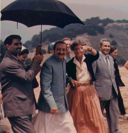 AVATAR MEHER BABA taking a tour of Meher Mount on August 2, 1956, with caretaker Agnes Baron. Close disciple Eruch Jessawalla is holding the umbrella.