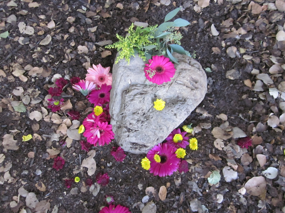 A HEART-SHAPED ROCK and flowers mark the spot under Baba's Tree where Avatar Meher Baba sat in 1956. (Margaret Magnus photo.)